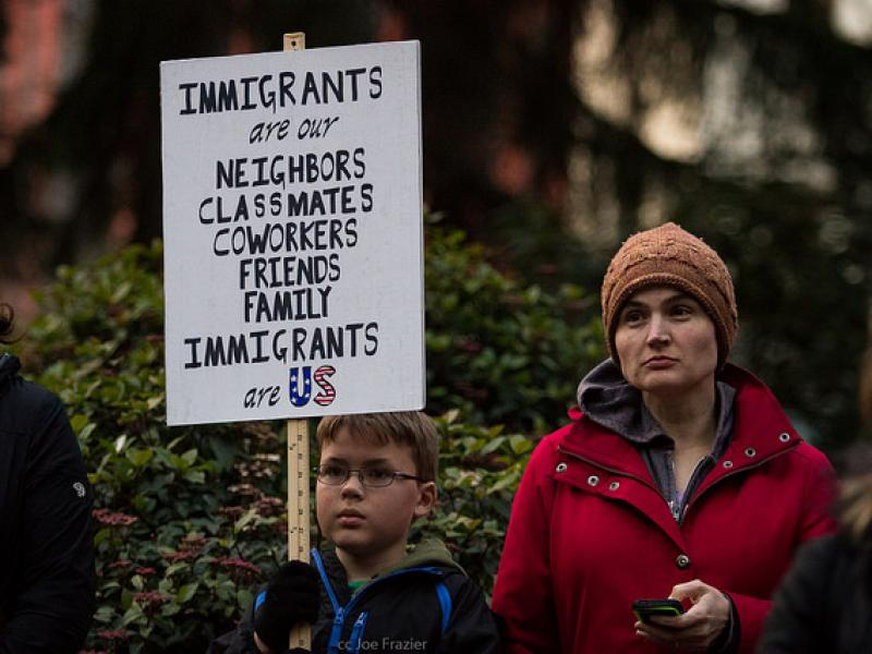 A child holds a sign that says immigrants are our neighbors