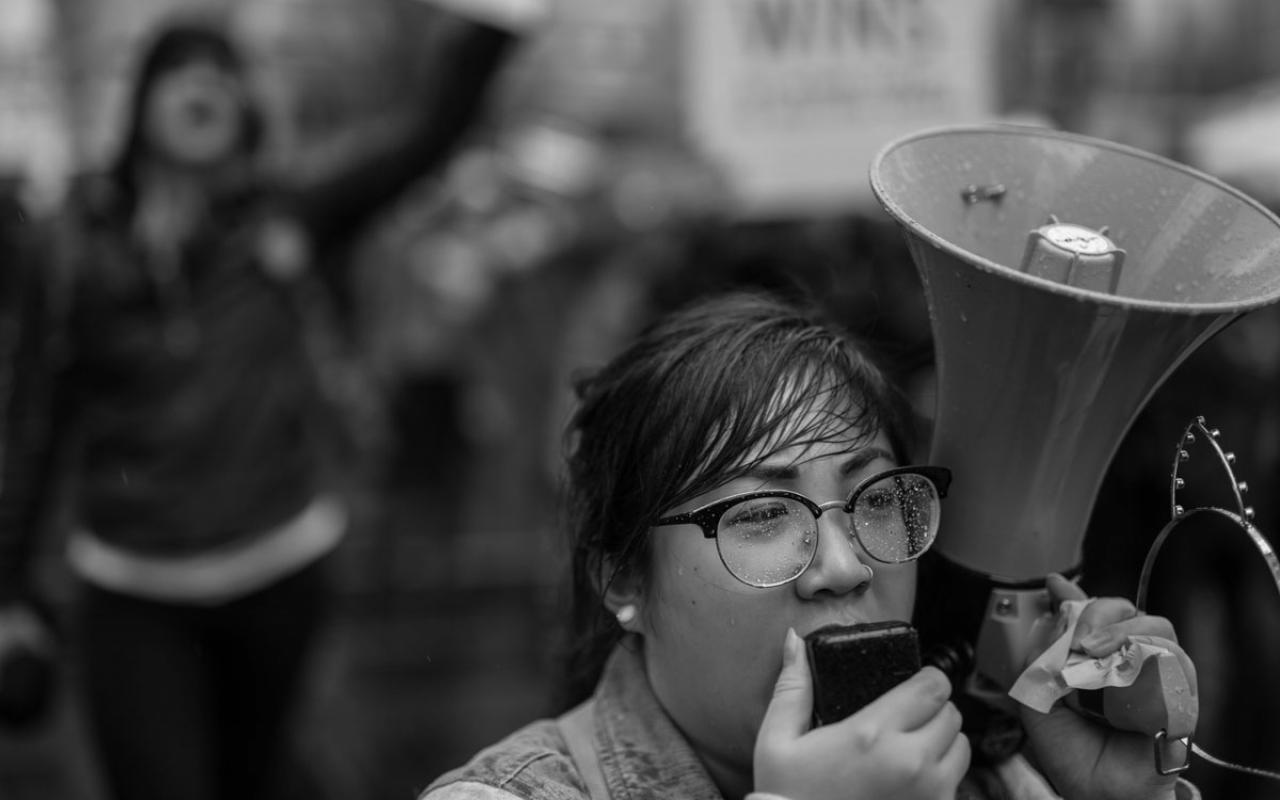 "A demonstrator speaking into a bull horn during the ""Strengthening Action for Justice."" convening. Photo credit: Jamie Francis"