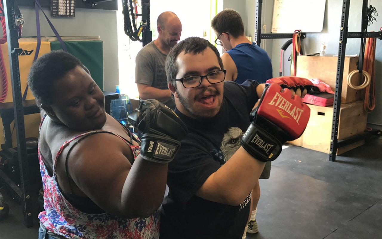 On-The-Move participants, Elizabeth and Spencer, flex their muscles after boxing at a local gym. Photo courtesy of On-The-Move Community Integration