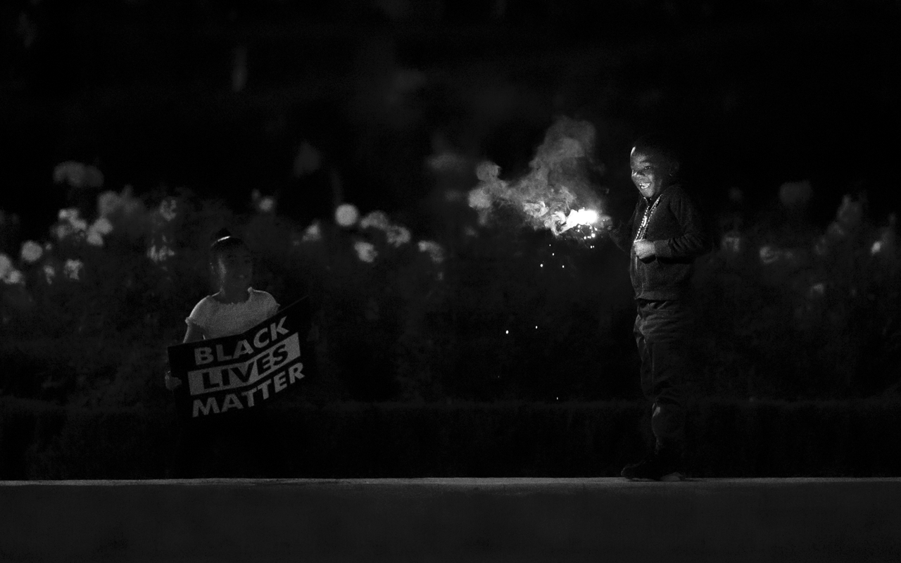 "Photo caption: Two siblings—one holding a sparkler and the other a sign that reads ""Black Lives Matter""—stand in solidarity at a violin vigil in Portland for Elijah McClain. Photo credit: Fred Joe Photo"